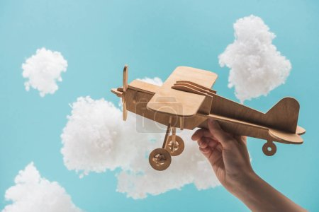 Photo for Wooden toy plane flying among white fluffy clouds made of cotton wool isolated on blue - Royalty Free Image