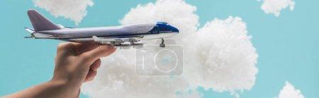 Foto de Vista recortada de la mujer jugando con el avión de juguete entre las nubes esponjosas blancas hechas de algodón aislado en azul, tiro panorámico - Imagen libre de derechos