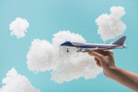 Foto de Vista recortada de la mujer jugando con el avión de juguete entre las nubes esponjosas blancas hechas de algodón aislado en azul - Imagen libre de derechos