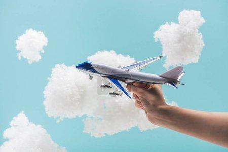 Photo pour Vue recadrée de la femme jouant avec l'avion jouet parmi les nuages duveteux blancs en laine de coton isolé sur bleu - image libre de droit