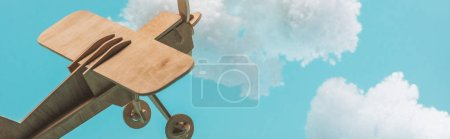Photo for Wooden toy plane flying among white fluffy clouds made of cotton wool isolated on blue, panoramic shot - Royalty Free Image
