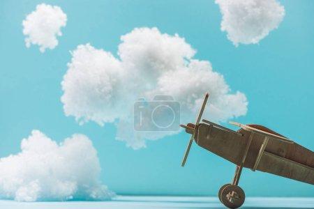 Foto de Avión de juguete de madera entre nubes de lana de algodón blanqueadas y aisladas en azul. - Imagen libre de derechos