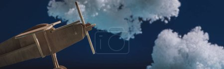 Photo pour Avion jouet en bois volant parmi les nuages duveteux blancs en laine de coton isolé sur bleu foncé, vue panoramique - image libre de droit