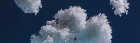 Foto de Nubes suaves blancas hechas de lana de algodón aislada en azul oscuro, tiro panorámico. - Imagen libre de derechos