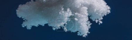 Photo for White fluffy cloud made of cotton wool isolated on dark blue, panoramic shot - Royalty Free Image