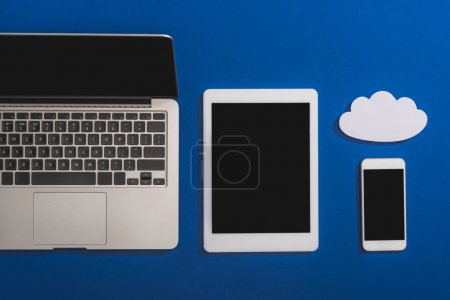 top view of empty white paper cloud near laptop, smartphone and digital tablet with blank screen isolated on blue