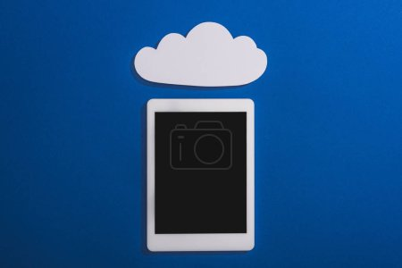 top view of empty white paper cloud near digital tablet with blank screen isolated on blue