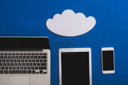 Photo pour Vue en haut d'un nuage de papier blanc vide près d'un ordinateur portable, d'un téléphone intelligent et d'une tablette numérique avec écran vierge isolé en bleu - image libre de droit