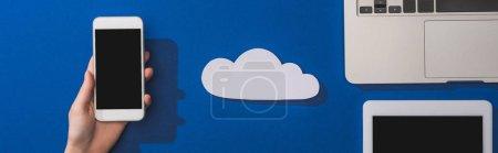 Photo pour Crochet vue d'une femme tenant un smartphone près d'un nuage de papier blanc vide et d'un ordinateur portable avec une tablette numérique sur fond bleu, photo panoramique - image libre de droit