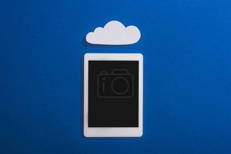 Foto de Vista superior de la nube vacía de papel blanco cerca de la tableta digital con pantalla en blanco en azul. - Imagen libre de derechos