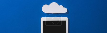 Photo for Top view of empty white paper cloud near digital tablet with blank screen on blue, panoramic shot - Royalty Free Image