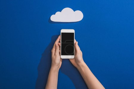 Photo for Cropped view of woman holding smartphone near empty white paper cloud on blue - Royalty Free Image