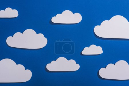 top view of white paper cut clouds on blue background