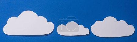 Photo pour Vue du dessus des nuages coupés en papier blanc sur fond bleu, vue panoramique - image libre de droit