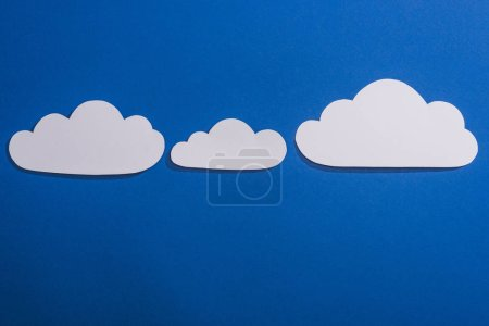 Photo for Top view of white paper cut clouds on blue background - Royalty Free Image