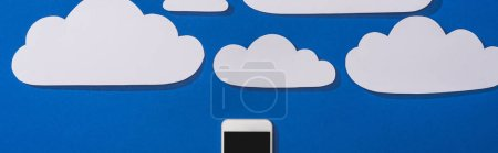 top view of white paper cut clouds and smartphone on blue background, panoramic shot