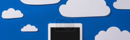 Photo for Top view of white paper cut clouds and digital tablet on blue background, panoramic shot - Royalty Free Image