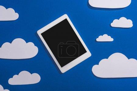Photo pour Vue du dessus des nuages de papier blanc coupés et tablette numérique sur fond bleu - image libre de droit