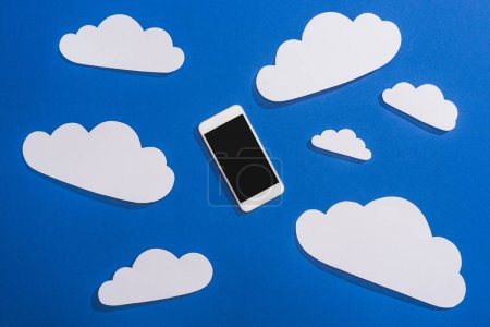 top view of white paper cut clouds and smartphone on blue background