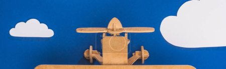 top view of wooden plane in blue sky with paper cut white clouds, panoramic shot