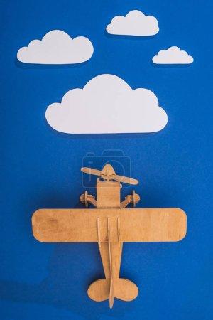 Photo pour Vue du dessus de l'avion jouet en bois dans le ciel bleu avec du papier coupé nuages blancs - image libre de droit