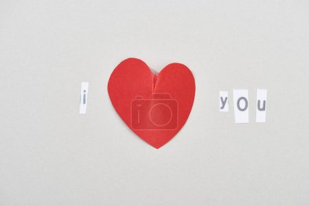 Top view of i love you lettering with heart shaped paper on grey background