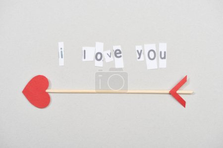 Photo for Top view of i love you lettering with arrow on grey background - Royalty Free Image