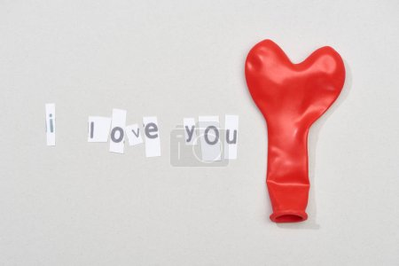 Photo pour I love you lettering with red balloon on grey background - image libre de droit