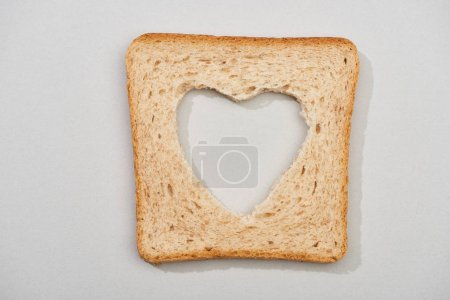 Photo for Top view of bread slice with carved heart shape on grey background - Royalty Free Image
