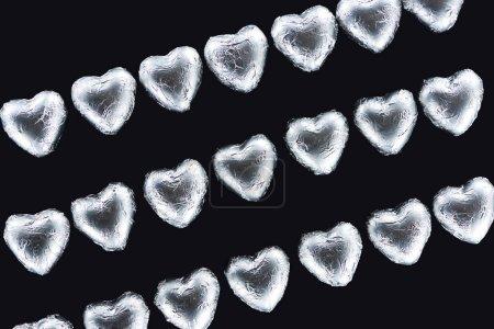 Foto de Vista superior de las líneas de dulces en forma de corazón en lámina aislada en negro - Imagen libre de derechos