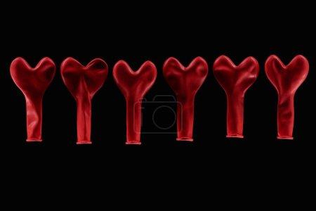 Photo pour Vue supérieure de ballons en forme de coeur rouge isolés sur fond noir - image libre de droit