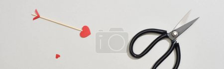 Photo for Top view of scissors and arrow with heart shape on grey background, panoramic shot - Royalty Free Image