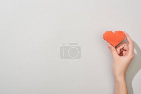 Photo pour Vue du dessus de la fille tenant coeur en papier sur fond gris avec espace de copie - image libre de droit