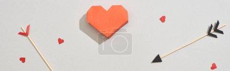 Foto de Vista superior de los papeles en forma de corazón con flechas sobre fondo gris, tiro panorámico. - Imagen libre de derechos