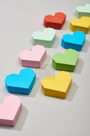 Foto de Líneas con papeles coloridos en forma de corazón sobre fondo gris - Imagen libre de derechos