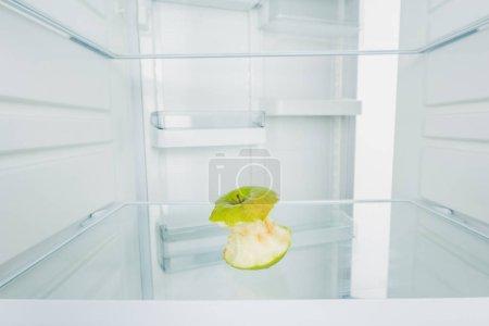 Photo pour Pomme verte à franges sur l'étagère du réfrigérateur avec porte ouverte isolée sur blanc - image libre de droit