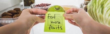 Photo pour Photo panoramique d'une femme tenant une carte avec manger plus de fruits lettrage avec aliments au réfrigérateur à l'arrière-plan, isolée sur blanc - image libre de droit