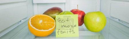 Photo pour Vue panoramique des fruits frais et du chariot avec consommation de plus de fruits lettrage sur les tablettes du réfrigérateur - image libre de droit