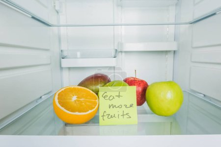 Photo pour Carte avec manger plus de fruits lettrage avec fruits au réfrigérateur - image libre de droit