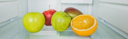 Photo pour Tournée panoramique de mangue fraîche avec pommes et tranche d'orange sur les tablettes du réfrigérateur - image libre de droit