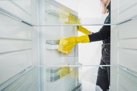 Photo pour Vue recadrée de la femme dans des gants en caoutchouc nettoyage réfrigérateur isolé sur blanc - image libre de droit