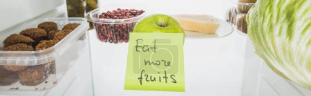 Photo for Panoramic shot of card with eat more fruits lettering in fridge with food isolated on white - Royalty Free Image
