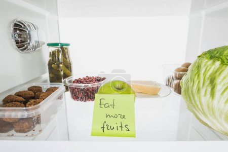 Photo pour Carte avec manger plus de fruits lettrage au réfrigérateur étagère avec aliments isolés sur blanc - image libre de droit
