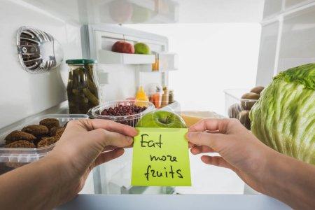 Photo pour Vue agrandie d'une femme tenant une carte avec manger plus de fruits lettrage avec aliments dans le réfrigérateur isolé sur blanc - image libre de droit