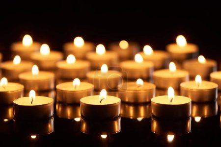 Photo for Selective focus of burning candles glowing in darkness - Royalty Free Image