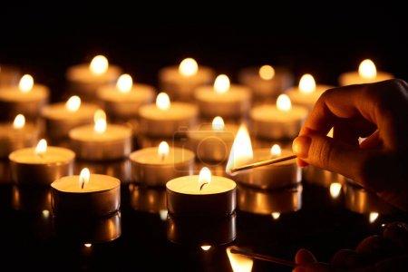 Foto de Enfoque selectivo de la mujer iluminando la vela con el partido en la oscuridad - Imagen libre de derechos