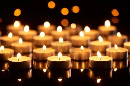 Photo pour Foyer sélectif de bougies allumées luisant dans l'obscurité avec des feux à boucle - image libre de droit
