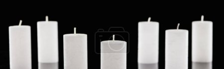 selective focus of white candles isolated on black, panoramic shot