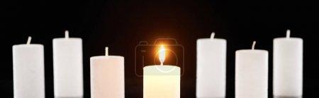 Photo pour Foyer sélectif de brûler des bougies blanches luisant près d'un autre isolé sur noir, plan panoramique - image libre de droit