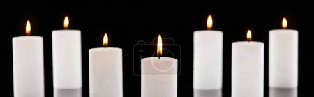 selective focus of burning white candles glowing isolated on black, panoramic shot